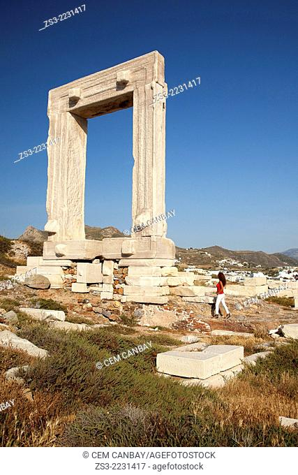 Woman near Portara, the giant door of the unfinished Apollon Temple on Palatia Islet in Naxos island, Cyclades Islands, Greek Islands, Greece, Europe