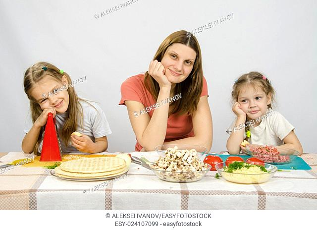 Satisfied mother with two daughters sitting resting his head in his hands at the table with the products for pizza