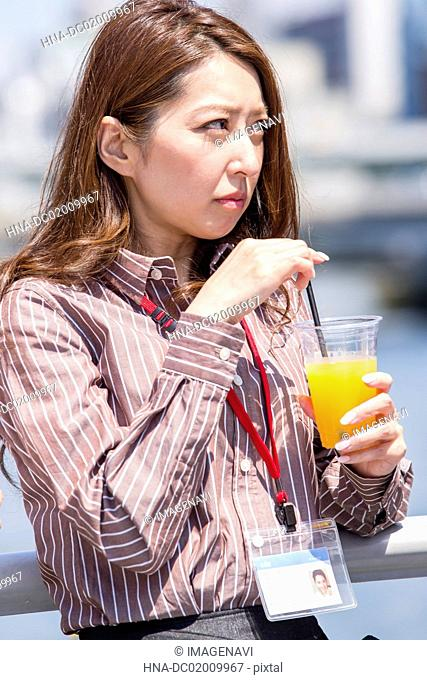Business woman having a glass of juice outside