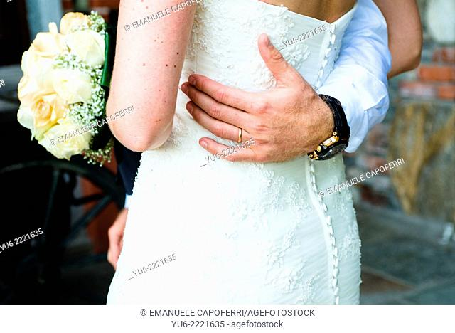 Hand of groom and bride embracing
