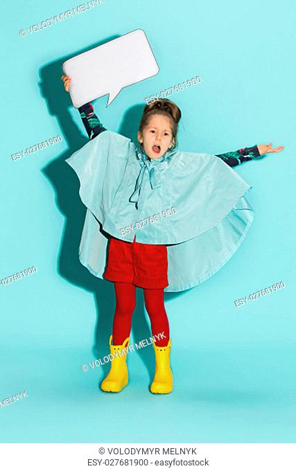 Little girl posing in fashion style wearing autumn clothing on blue background with empty blank. Rubber yellow boots