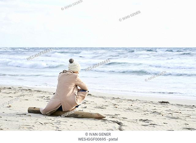 Spain, Menorca, back view of senior woman wearing bobble hat and coat sitting on the beach in winter