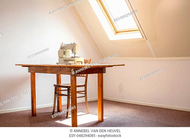 Sewing machine on table in a atelier studio, workplace or hobby room retro