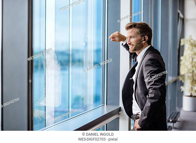 Relaxed businessman with bluetooth headset standing in his office looking out of the window
