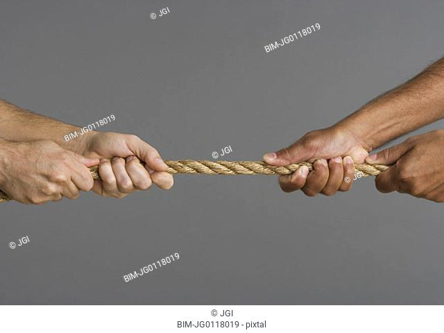 Close up of tug-o-war with four hands