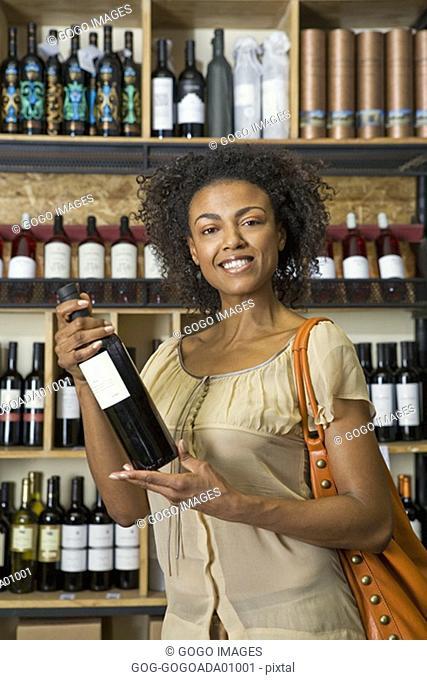 Woman displaying wine bottle