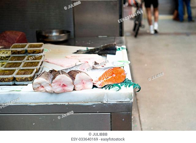 Fresh salmon cuts and other packaged foods on display on street vendor table outdoors