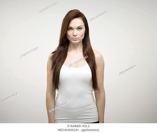 Portrait of young woman standing against white background