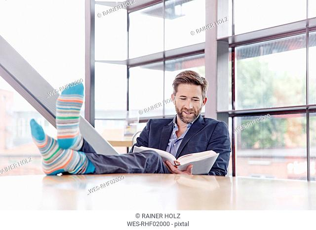 Businessman putting his feet on the table reading book