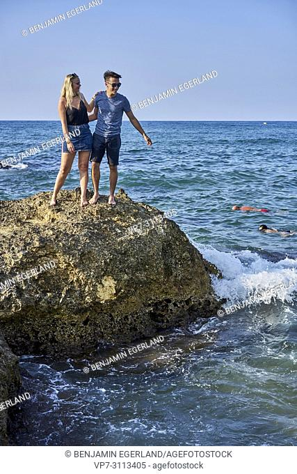 couple on rock at beach. In holiday destination Chersonissos, Crete, Greece