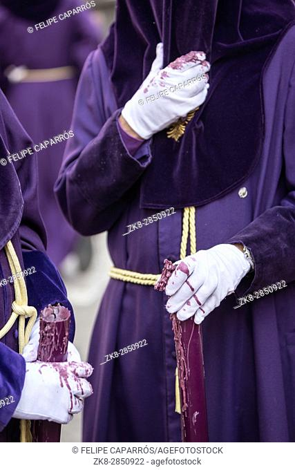 Detail penitent white holding a candle during Holy Week, Spain