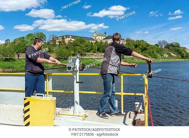Young men operating ferryboat on Bug river in Drohiczyn, Poland