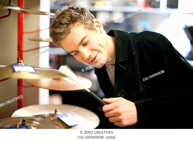 Young male trying drum kit in music store