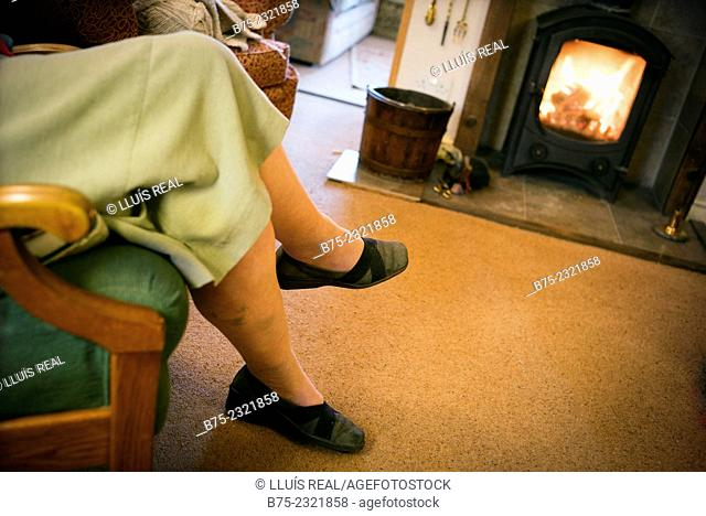 Closeup of an elderly lady legs resting sitting in an armchair near a wood stove on a cottage in Yorkshire, England, UK