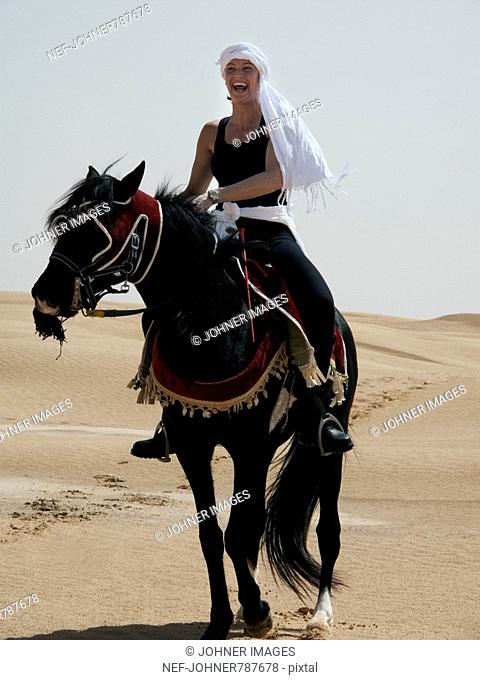 Woman riding a horse in the desert, Tunisia