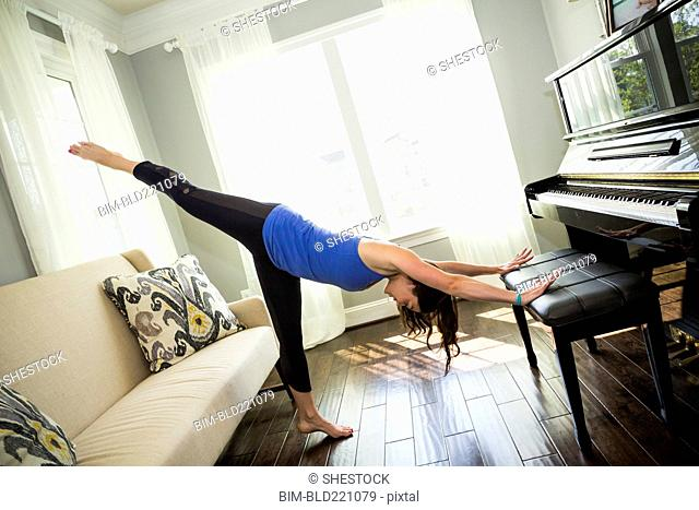 Woman stretching on piano bench