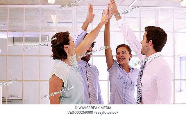 Business team high fiving together