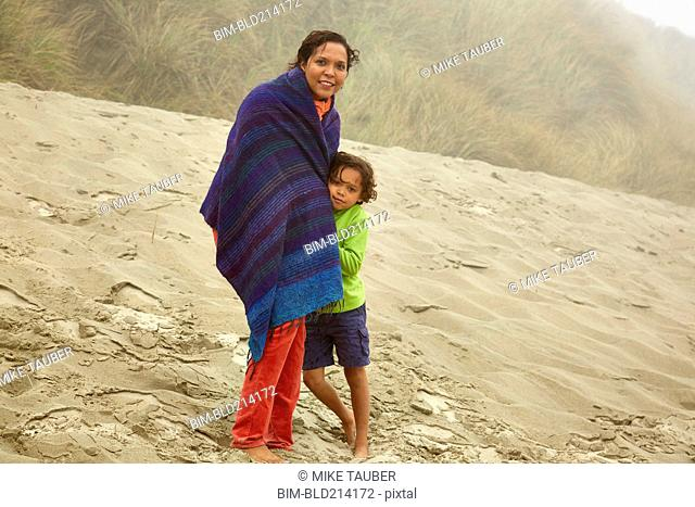 Mixed race mother and son hugging on beach