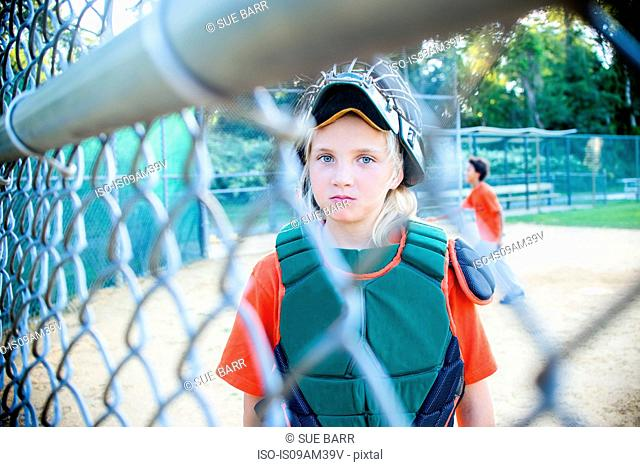 Young girl wearing baseball kit, looking through fence