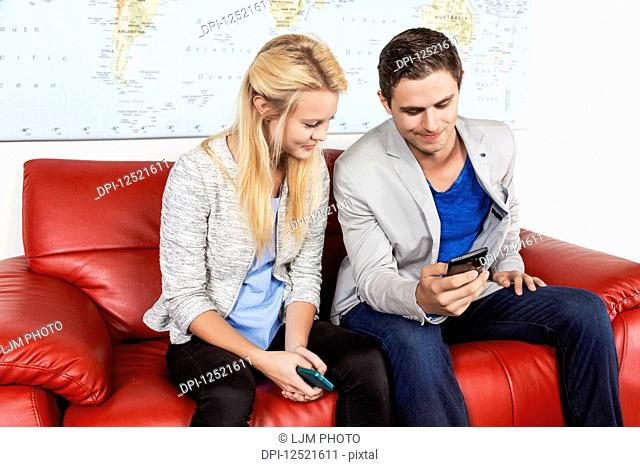 Two young millennial business professionals in the lobby of their workplace using their smart phones while taking a break; Sherwood Park, Alberta, Canada