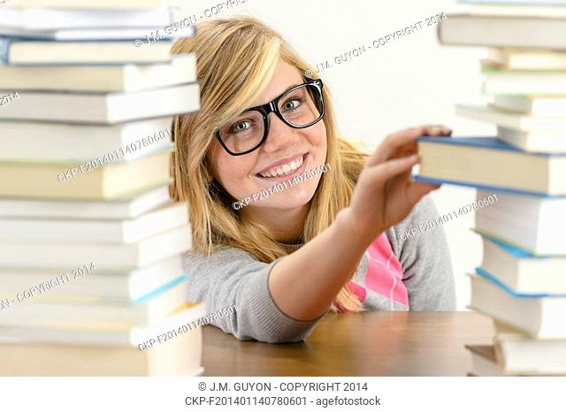 Smiling student girl with glasses take book from stack