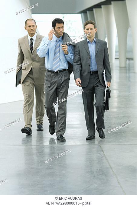 Three businessmen walking through lobby, one using cell phone