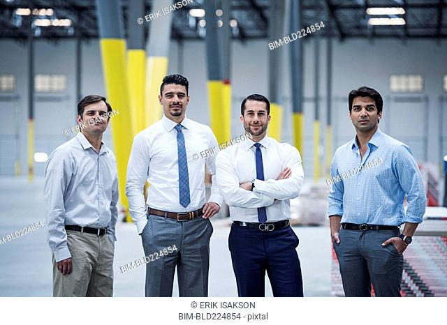 Smiling businessmen posing in empty warehouse