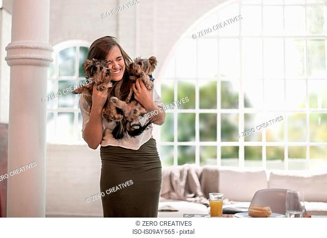 Happy woman hugging pet dogs at home