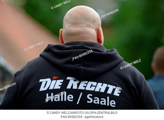 "A participant of Thuegida march is wearing a hooded jumper that reads """"Deutschland zuerst - Invasoren stoppen"""" (""""Germany first - stop invaders) above a logo..."