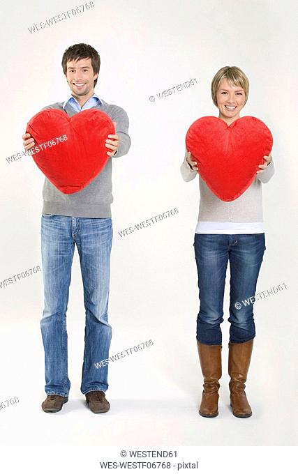 Young couple holding heart-shaped cushions, portrait