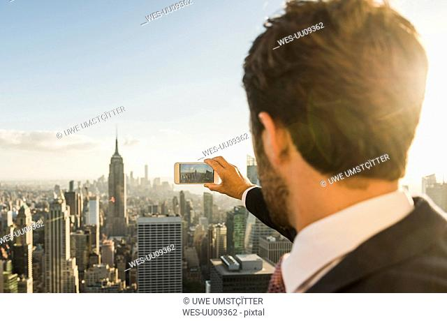 USA, New York City, man taking cell phone picture on Rockefeller Center observation deck