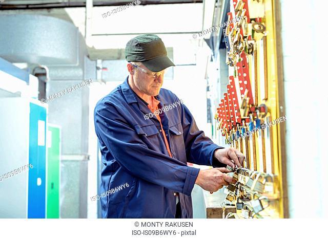 Locomotive engineer inspecting safety padlocks in train works