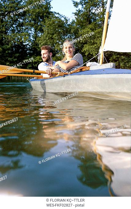 Young couple enjoying a trip in a canoe with sail on a lake