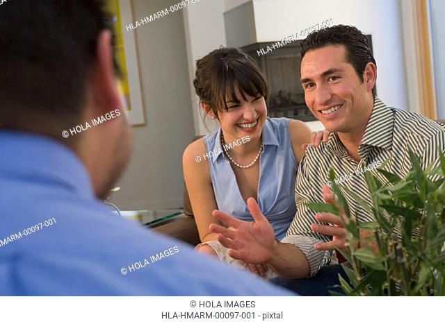 Mid adult man and a young woman talking to a real estate agent