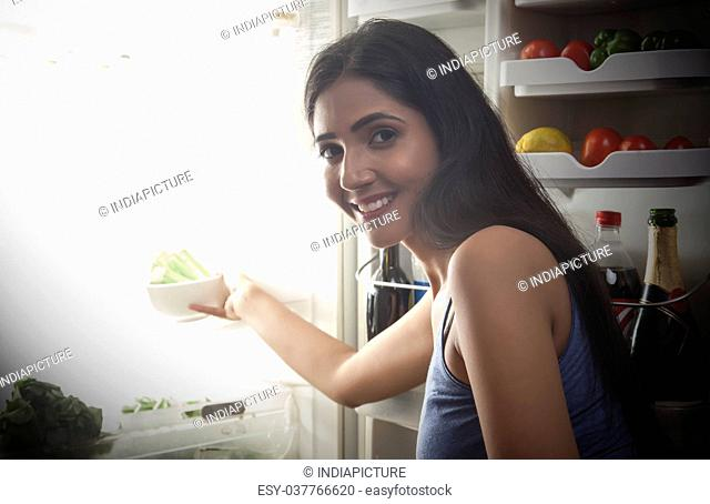Close-up of smiling young woman keeping food in the fridge at night