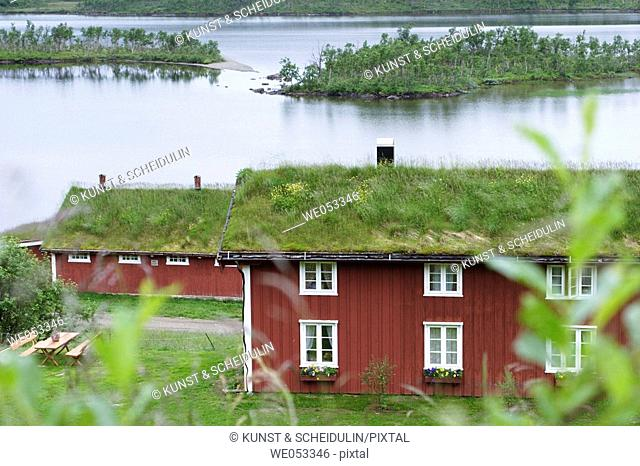 Traditional red wooden farm-house with grass-roof. Lake Rauvatnet, Fjell near Mo i Rana, Nordland, Lapland, Norway, Scandinavia, Europe