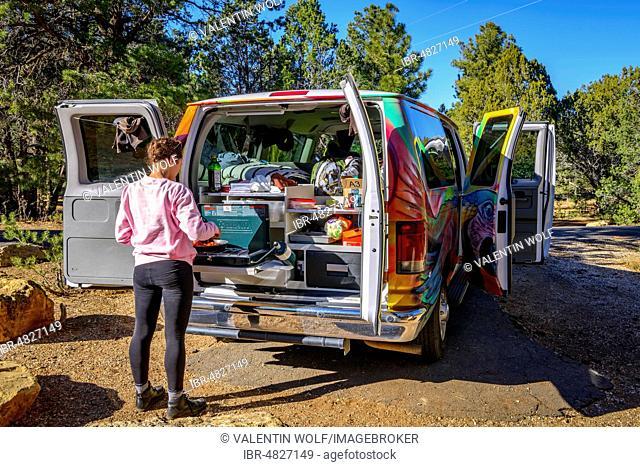 Young woman cooking at the gas stove of a camping van, campervan, camping, RV, Mather Campground, Grand Canyon National Park, South Rim, near Tusayan, Arizona