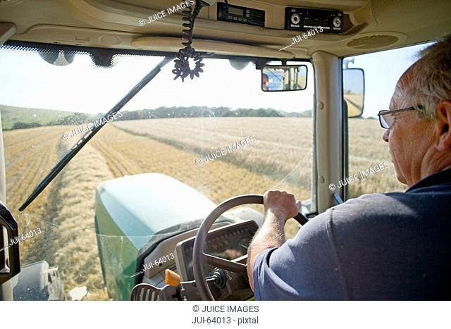 Farmer at steering wheel of tractor in sunny rural field
