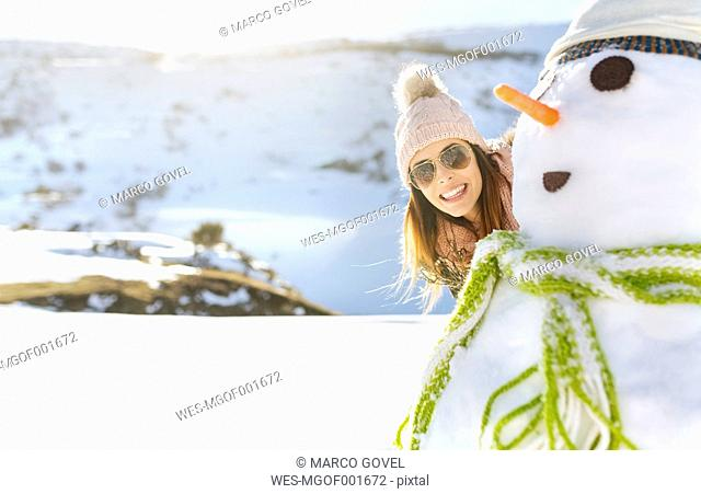 Spain, Asturias, happy young woman with a snowman