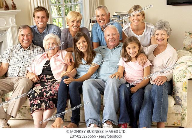 Large Family Group Sitting On Sofa Indoors