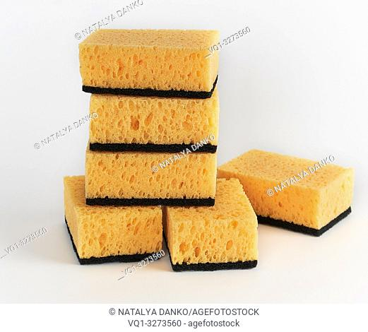 stack of yellow kitchen sponges for washing dishes on a white background