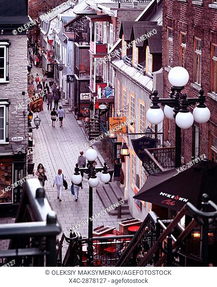 People walking in historic streets Rue du Petit Champlain and Rue Sous Le Fort of old Quebec City in the evening, view from above. Quebec, Canada