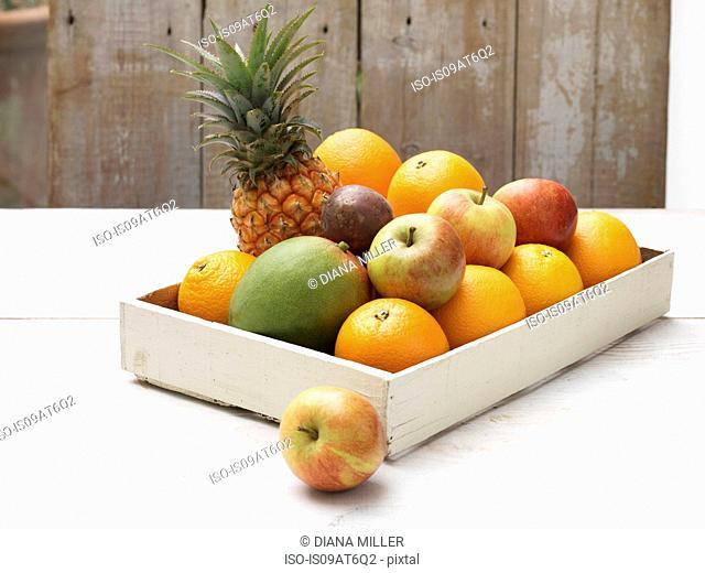 Crate of fruit on whitewashed wooden table