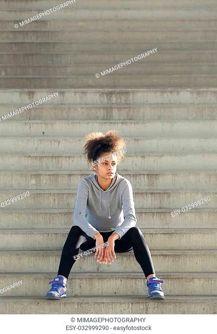 Portrait of a young sports woman sitting on stairs outdoors