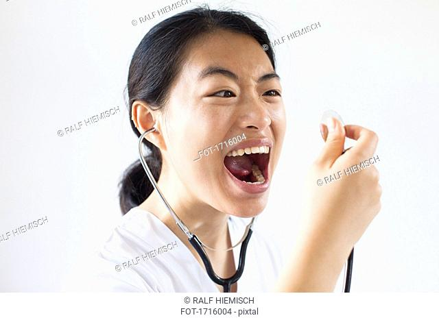 Frustrated doctor screaming with mouth open into stethoscope against white wall