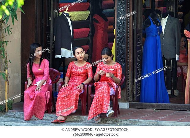 Young women tailor shop assistants wait for customers Hoi An Vietnam