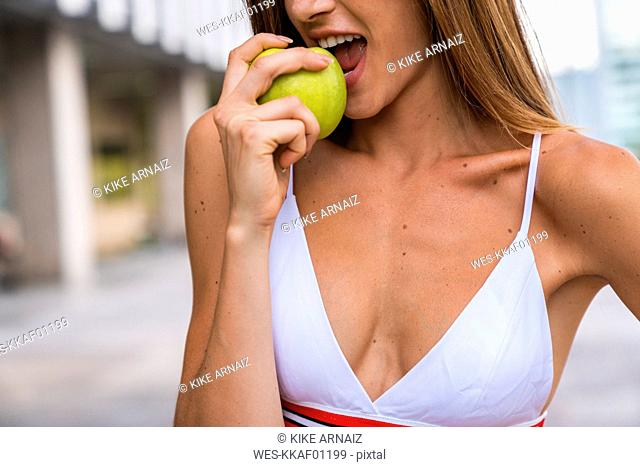 Close-up of young woman wearing sports bra eating an apple