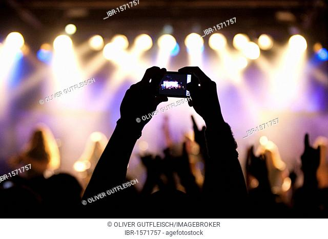 A fan takes a picture with small digital camera at the concert of Swiss pagan metal band Eluveitie live in the Schueuer venue, Lucerne, Switzerland
