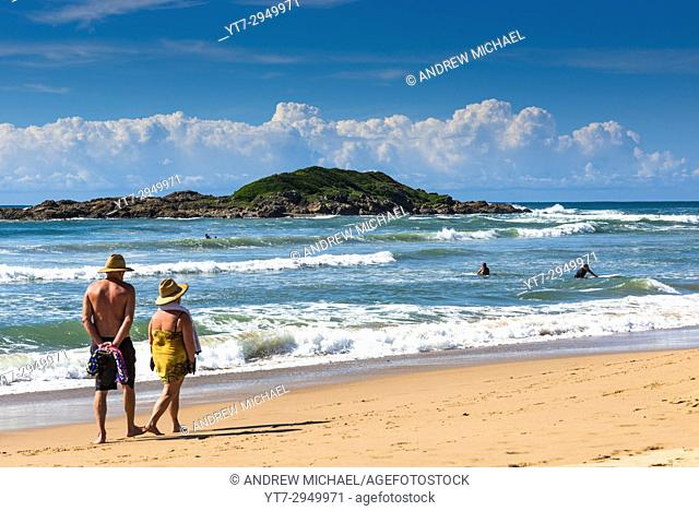 Couple look out to Little Mutton bird Island from Park beach, Coffs Harbour, NSW, Australia