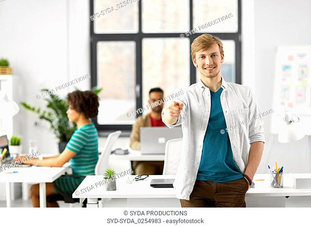 happy smiling man pointing finger at you at office